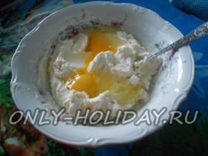 Разминаем творог в однородную пастообразную массу. Добавляем сахар, ваниль, сметану, соду и два крупных куриных яйца.