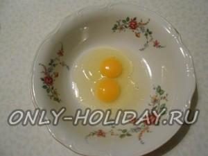 Влить в миску два сырых куриных яйца.