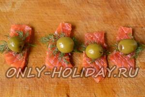 Рыбу нарезать слайсами, положить оливку и зелень, свернуть рулетиками