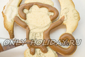 На печенье намечаем контуры обезьяны с бананами. Закрашиваем коричневые детали