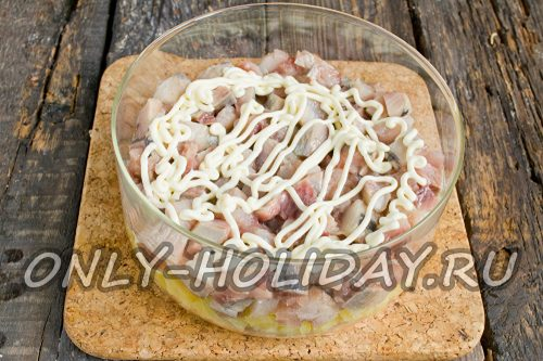сельдь нарезать кусочками, выложить на картофель и смазать майонезом