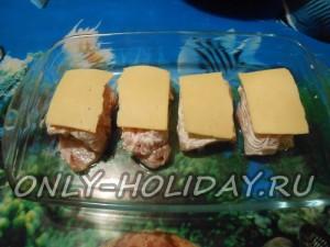 Куриные рулетики с яблоками накрываем пластинками сыра и выпекаем в духовке