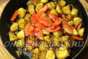 В сковороду с карри добавить крупнорезанный помидор
