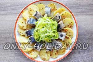 В центр картофельного салата с селедкой поместить маринованный лук-порей
